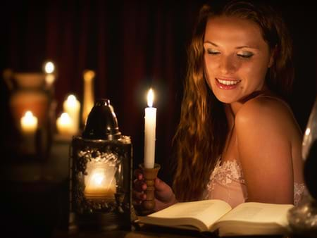 beautiful woman reading an erotic book by candlelight
