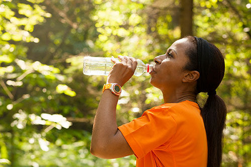 woman drinking water while exercising in the woods