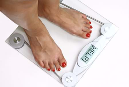 woman standing on bathroom scale needs weight loss tips