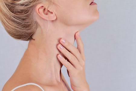 a woman touching her neck where her thyroid is.