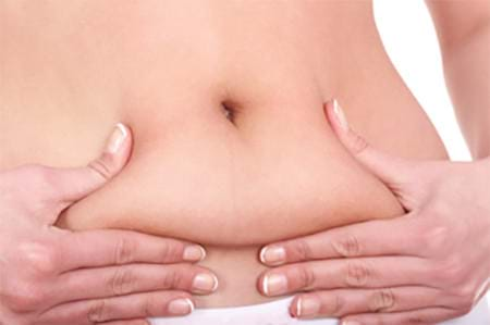woman's hand squeezing her belly fat